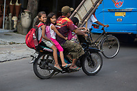 Yogyakarta, Java, Indonesia.  Three Girls and Father on a Motorbike, no Helmets.