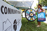 Sydnee Howard, 6, visits the City of Fayetteville Community Resources booth, Friday, July 30, 2021, to spin a wheel for a prize during the annual CDBG in the Park picnic at Walker Park in Fayetteville. The city's Community Development Block Grant program received $748,785 from the federal government this year and pays for a variety of programs, including housing rehabilitation, taxi passes, Ranger's Pantry AniMeals and the Hearth program to house residents. Check out nwaonline.com/210731Daily/ and nwadg.com/photos for a photo gallery.(NWA Democrat-Gazette/David Gottschalk)