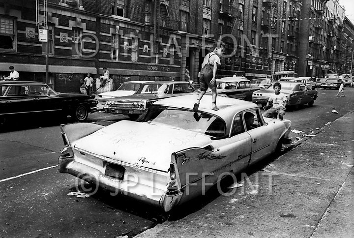 Bronx, New York City, NY. Summer of 1966. <br /> An abandoned car becomes a place for kids to play in Fox Street.<br /> From the mid-1960s to the late-1970s, quality of life for Bronx residents declined sharply.