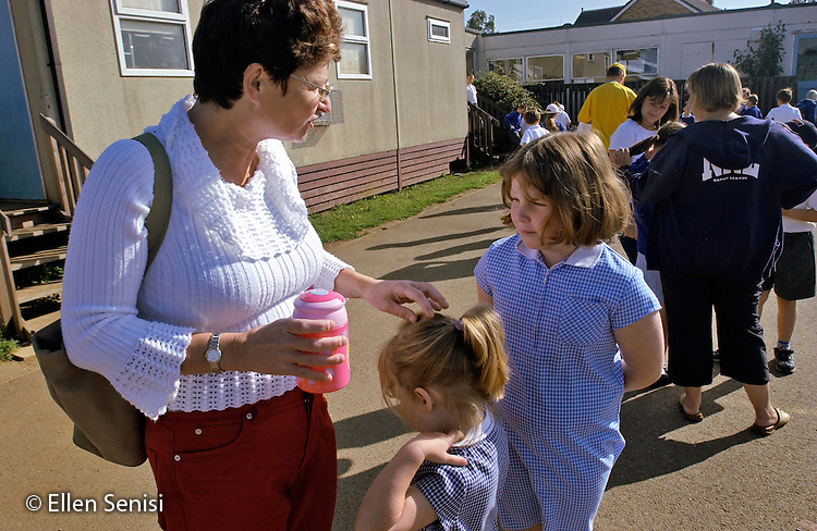 MR / Abingdon, Oxfordshire, England.Thomas Reade Primary School.Mother talks to her daughters (5, 9) as she drops them off at school on her way to work..MR: Web2 Web3 Web4.©Ellen B. Senisi