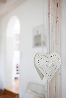 A tin heart with punched decoration hangs from the distressed wooden frame of a mirror in the living room