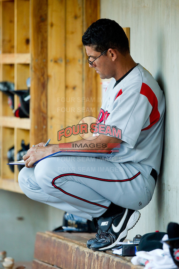 Carolina Mudcats hitting coach Rouglas Odor (24) updates his notes during the Carolina League game against the Winston-Salem Dash at BB&T Ballpark on July 25, 2013 in Winston-Salem, North Carolina.  The Mudcats defeated the Dash 5-4.  (Brian Westerholt/Four Seam Images)