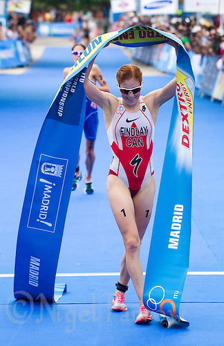 05 JUN 2011 - MADRID, ESP - Paula Findlay celebrates victory at the Madrid round of the women's ITU World Championship series as runner up Helen Jenkins approaches the finish line.(PHOTO (C) NIGEL FARROW)