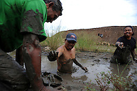 Villagers from Besuki fishing in the mud at the base of the surrounding dam. Since May 2006, more than 10,000 people in the Porong subdistrict of Sidoarjo have been displaced by hot mud flowing from a natural gas well that was being drilled by the oil company Lapindo Brantas. The torrent of mud - up to 125,000 cubic metres per day - continued to flow three years later.