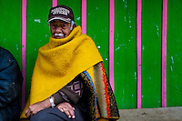 A Colombian man, wearing poncho and the Narcotics Officer cap, sits in front of his house in the slum of Ciudad Bolívar, Bogota, 28 May 2010.