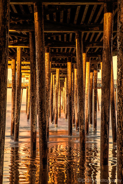 Underneath the Pismo Beach Pier at sunrise with the warm glow of the sun's rays on the pier
