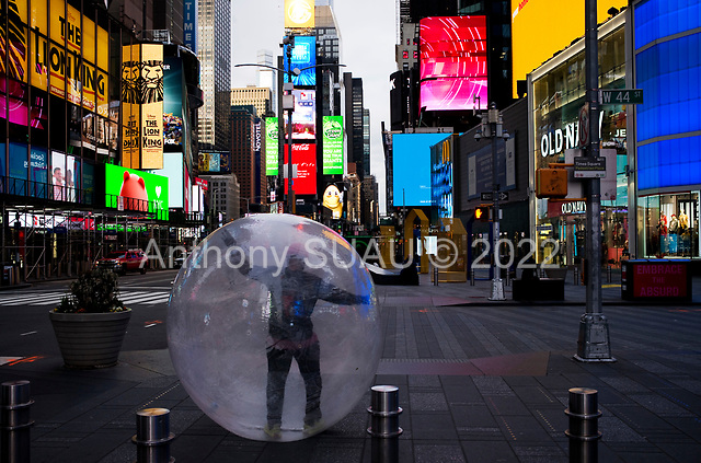 """New York, New York<br /> April 4, 2020<br /> <br /> A man walks Times Square in a plastic bubble to avoid the corona virus exposure.<br /> <br /> The coronavirus has transformed urban architectural spaces with fear of proximity. Not entirely void of humanity, social distancing, within expansive city environments has created a landscape of aggrandizing physical structures and expanding spaces while diminishing the scale of humans. Face masks enhance the anonymity of """"the person"""", reducing them to a figure or an uninterrupted shadow falling on a surface."""