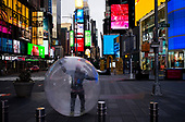 "New York, New York<br /> April 4, 2020<br /> <br /> A man walks Times Square in a plastic bubble to avoid the corona virus exposure.<br /> <br /> The coronavirus has transformed urban architectural spaces with fear of proximity. Not entirely void of humanity, social distancing, within expansive city environments has created a landscape of aggrandizing physical structures and expanding spaces while diminishing the scale of humans. Face masks enhance the anonymity of ""the person"", reducing them to a figure or an uninterrupted shadow falling on a surface."