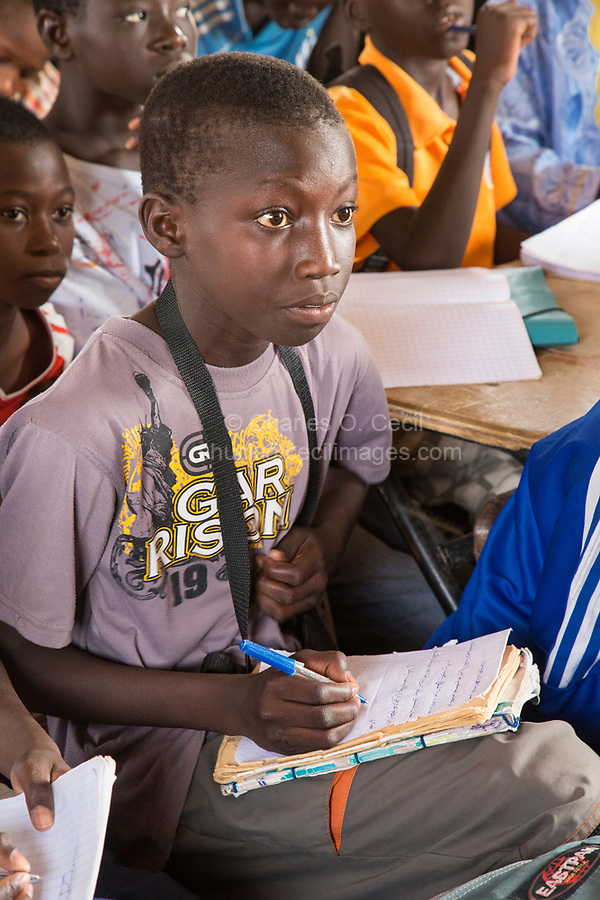 Senegal, Touba.  Young Student at Al-Azhar Madrasa, a School for Islamic Studies, Copying Material in Arabic into his Notebook.