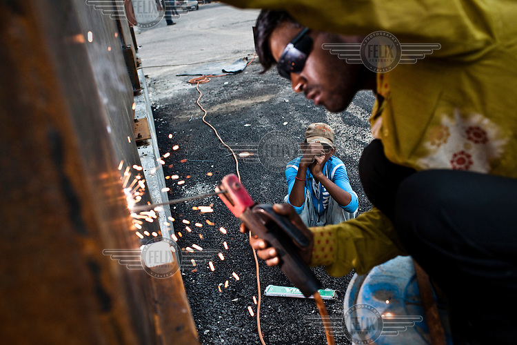 A labourer welds the metal wall of the car park of Jawaharlal Nehru Stadium, the main stadium of the approaching 2010 Commonwealth Games.