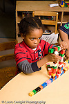 Education Preschool 4-5 year olds boy making construction of locking plastic colored cubes vertical