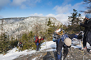 Group of winter hikers ascending a steep section along the Mt Parker Trail, near the summit of Mount Resolution, in the White Mountains, New Hampshire USA.