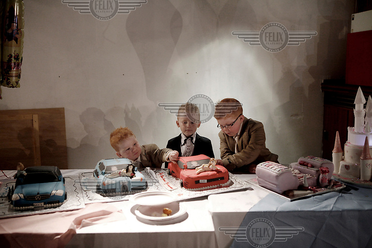 Irish Traveller children Dennis and Richard Sheridan, with their cousin Michael, pick at First Holy Communion cakes as they celebrate their First Holy Communion at the Skylark Hotel.