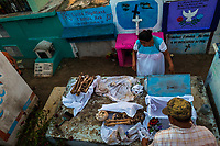 """Mayan peasants clean dried-up bones of a deceased family member during the bone cleansing ritual at the cemetery in Pomuch, Mexico, 29 October 2019. Every year on the Day of the Dead, people of Pomuch, a small Mayan community in the south of Mexico, visit the cemetery to take part in a pre-Hispanic tradition of cleaning of bones of their departed relatives (""""Limpia de huesos""""). People who die in Pomuch are firstly buried for three years in an above-ground tomb then the dried-up bodies are taken out, bones are separated, wrapped in a decorated cloth, put into a wooden crate, and placed on display among flowers for veneration."""