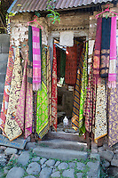 Bali, Indonesia.  Fabric for Sale, Pigeon in the Doorway, Tenganan Village.