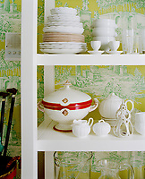 Simple, clean white shelving presents a mix of modern and antique crockery against the dramatic backdrop of an acid-coloured toile de jouy wallpaper.