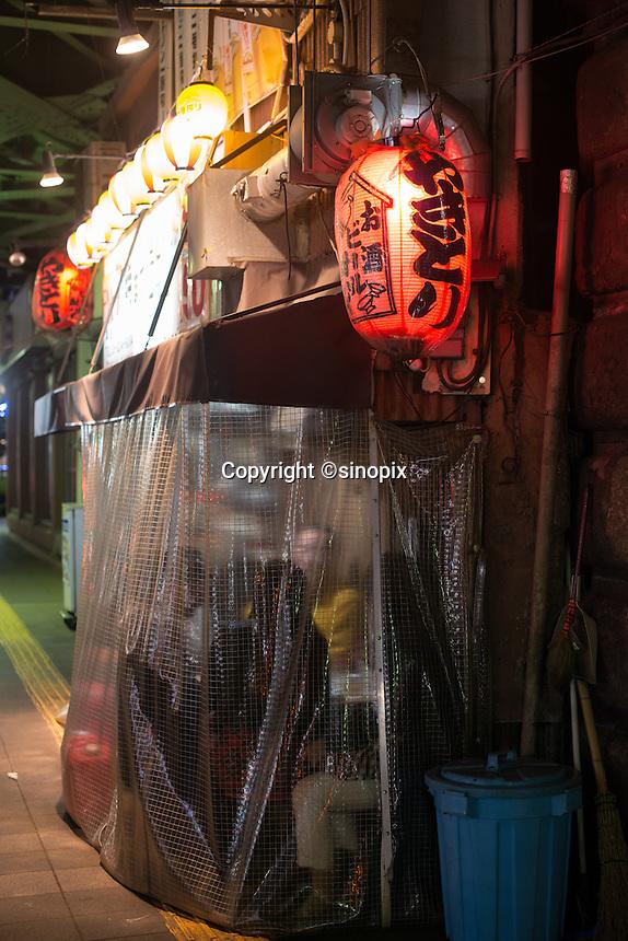 Salaryman enjoy drinking at the Yakitori bars under the railway track  at Shinbashi station