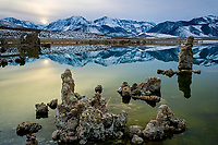 A fine art landscape image of a wintry sunset reflecting pale yellow light and the Sierra mountain range in the calm waters of Mono Lake, in the Eastern Sierras region of California.  The textured contours of tufas in the foreground create contrast with the smooth lines of the lake and mountain reflections of blue shadows and white snow.