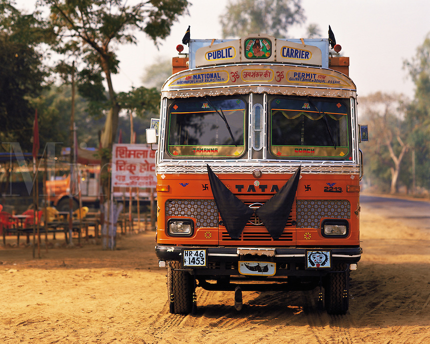 A brightly-painted public bus sits at a truck-stop on the main road between Agra and Jaipur, Indi