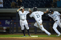 West Michigan Whitecaps Derek Hill (21) celebrates with Brett Pirtle (5) and Jose Azocar (27) after scoring the game winning run during a game against the Burlington Bees on July 25, 2016 at Fifth Third Ballpark in Grand Rapids, Michigan.  West Michigan defeated Burlington 4-3.  (Mike Janes/Four Seam Images)