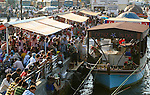 Istanbul, Turkey. People eating fish cooked on a boat in Eminonu district. Boat restaurants are popular in Istanbul and they serve a grilled fish fillet inserted in a half loaf of bread, onion and lemon juice.