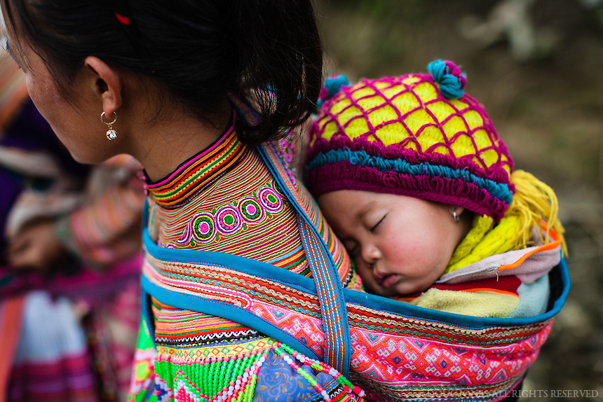 Weekly market days attract the women from different Hmong tribes in the hill country of northeastern Vietnam.  This Flower Hmong mother and her child are dressed in their finest handmade clothing for the big day.