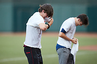 Two fans compete in a contest where they have to put on a wet t-shirt between innings of the High-A East game between the Greensboro Grasshoppers and the Winston-Salem Dash at Truist Stadium on August 13, 2021 in Winston-Salem, North Carolina. (Brian Westerholt/Four Seam Images)