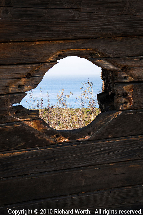 A hole in wreckage from the steam schooner Point Arena frames an ocean view at Ano Nuevo State Reserve on California's Coast.