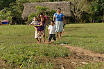 A Mayan family stroll from their thatched home in Midway village, Belize