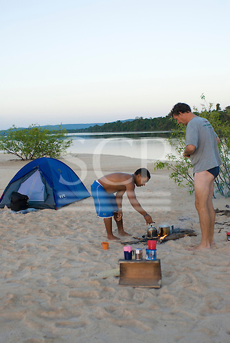 Pará State, Brazil. Xingu River. Patrick Cunningham and Gilson in camp, preparing food.