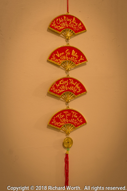 Hung in a place of prominence in a home, this Lunar New Year ornament features four decorative segments each with its own message of New Year's greeting:  wishes for a Happy New Year, wishes for business prosperity, wishes for personal prosperity.  Happy Year of the Dog.