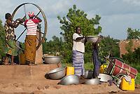 BURKINA FASO, Gaoua , women fetch drinking water from water pump with turning wheel in village / Burkina Faso, Gaoua, Frauen holen Wasser von einem Brunnen mit Drehpumpe