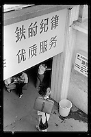 Chinese passengers count money as they wait to board a train in China's Shenzhen Special Economic Zone on the border with Hong Kong, 1987.