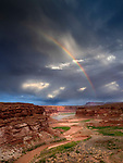 A rainbow appears over North Wash and the Colorado River in the Glen Canyon National Recreation Area near Hite, UT, USA