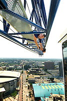 Photographer Patrick Schneider leans over the edge of a crane arm to capture high rise construction workers as they construct new skyscrapers downtown. Photos taken as part of a story package on crane construction.