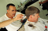 Professional barber cutting client's hair.
