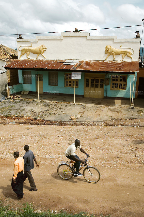 Rwanda. Southern province. Gitarama. District of Muhanga. Two black men walk on the dirt road, another rides his bicycle. A building, from the old colonial architectural style, with two golden lions on the wall. Rust on the metal roof. Daily life.   © 2007 Didier Ruef
