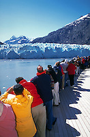 Tourists line up on the deck of a cruise ship to view glaciers in Glacier Bay National Park. Alaska.