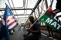 NEW YORK, USA - May 25: A man holds two Black Lives Matteren flag on the Brooklyn Bridge on the first anniversary of death on May 25, 2021 in New York City. George Floyd's assassination in Minneapolis sparked a worldwide outcry and continued to propel the Black Lives Matter movement through different cities in the United States and the world. (Photo by Pablo Monsalve / VIEWpress via Getty Images)