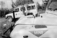 Albania. Province of Kruma. Lata. On the border between Albania and Kosovo. Swiss Foundation for Mine Action ( Fédération suisse de déminage - FSD). Mine -clearing and clearance operations of landmines and unexplosed ordnance (UXO). Two FSD Landrover jeep vehicles parked on the field in the safety zone. 20.09.03 © 2003 Didier Ruef