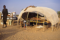 Akadaney, Central Niger, West Africa.  Fulani Nomads.  Fulani Woman alongside her Sleeping Shelter.  Eating and Food Storage Utensils are behind her.