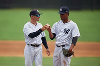 GCL Yankees East pitching coach Justin Pope (left) talks with pitcher Joensy Abreu (21) on a side field during a Gulf Coast League game against the GCL Phillies East on July 31, 2019 at Yankees Minor League Complex in Tampa, Florida.  GCL Phillies East defeated the GCL Yankees East 4-3 in the second game of a doubleheader.  (Mike Janes/Four Seam Images)