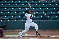 Yoelqui Cespedes (15) of the Winston-Salem Rayados follows through on his swing against the Llamas de Hickory at Truist Stadium on July 6, 2021 in Winston-Salem, North Carolina. (Brian Westerholt/Four Seam Images)