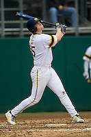 Michigan Wolverines first baseman Kendall Patrick (15) follows through on his swing during the NCAA baseball game against the Washington Huskies on February 16, 2014 at Bobcat Ballpark in San Marcos, Texas. The game went eight innings, before travel curfew ended the contest in a 7-7 tie. (Andrew Woolley/Four Seam Images)