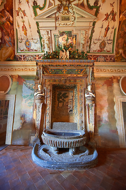 """Salon of the Fountain( Sala della Fontana ), the banquet hall of Cardinal Ipollito d""""Este. The trompe-l'?il frescoes were carried out by 6 assistants of Girolamo Muziano (1532-1592) were inspired by the """"Solomonic"""" winding columns of the Vatican Basilica to create a loggia decorated by festoons of fruit, flowers & vegetables with a landscape beyond. The rustic fountain at the end of the salon was built by fountain maker Curzio Maccarone and was completed in 1568. Villa d'Este, Tivoli, Italy. A UNESCO World Heritage Site."""