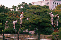 Japanese workers prune trees on the grounds of Osaka Castle. Osaka, Japan.