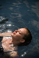 Young woman floating in water, eyes shut, elevated view
