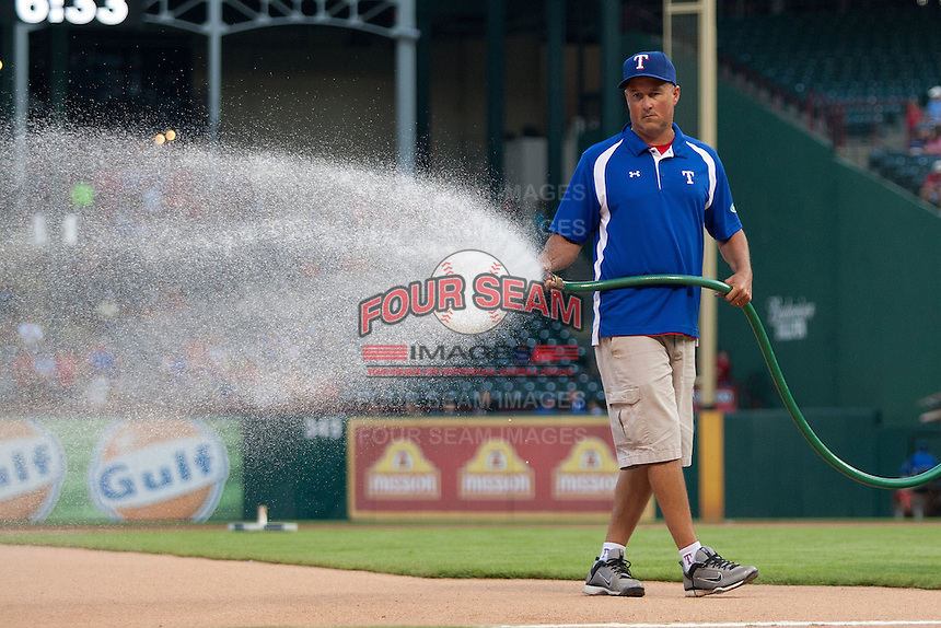 Texas Rangers head grounds keeper Dennis Klein prepares the field before the Major League Baseball game against the Baltimore Orioles on August 21st, 2012 at the Rangers Ballpark in Arlington, Texas. The Orioles defeated the Rangers 5-3. (Andrew Woolley/Four Seam Images).