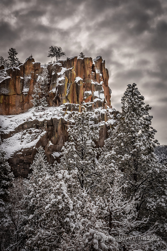Battleship Rock towers above snow covered pines under a brooding sky in the Jemez Mountains