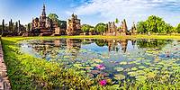 Wat Maha That temple and Buddha pond reflection with pink flower foreground, during morning golden hour, in Sukhothai Historical Park, Thailand